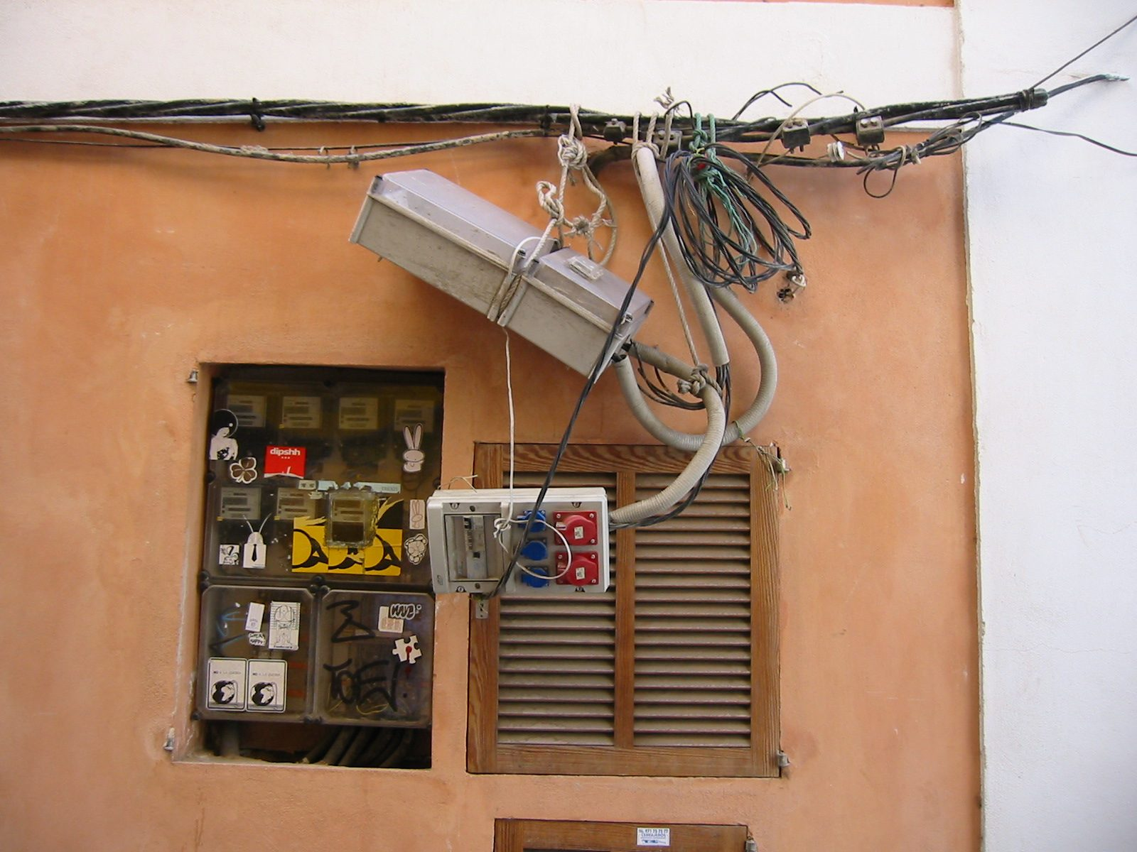 AMn sieht ein Gewirr von elektrischen Leitungen, die an Seilen hängen, mit Verteilerkästen, die fliegend aufgehängt sind. Das reinste Chaos! und ... außen!!!