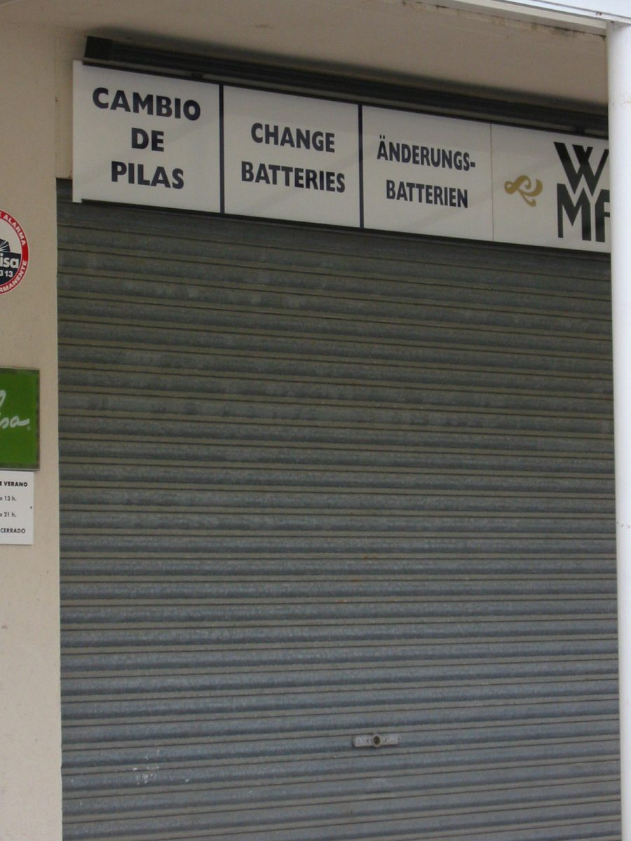 """Man sieht ein geschlossenes Ladentor über dem """"Änderungs-Batterie"""" prangt."""
