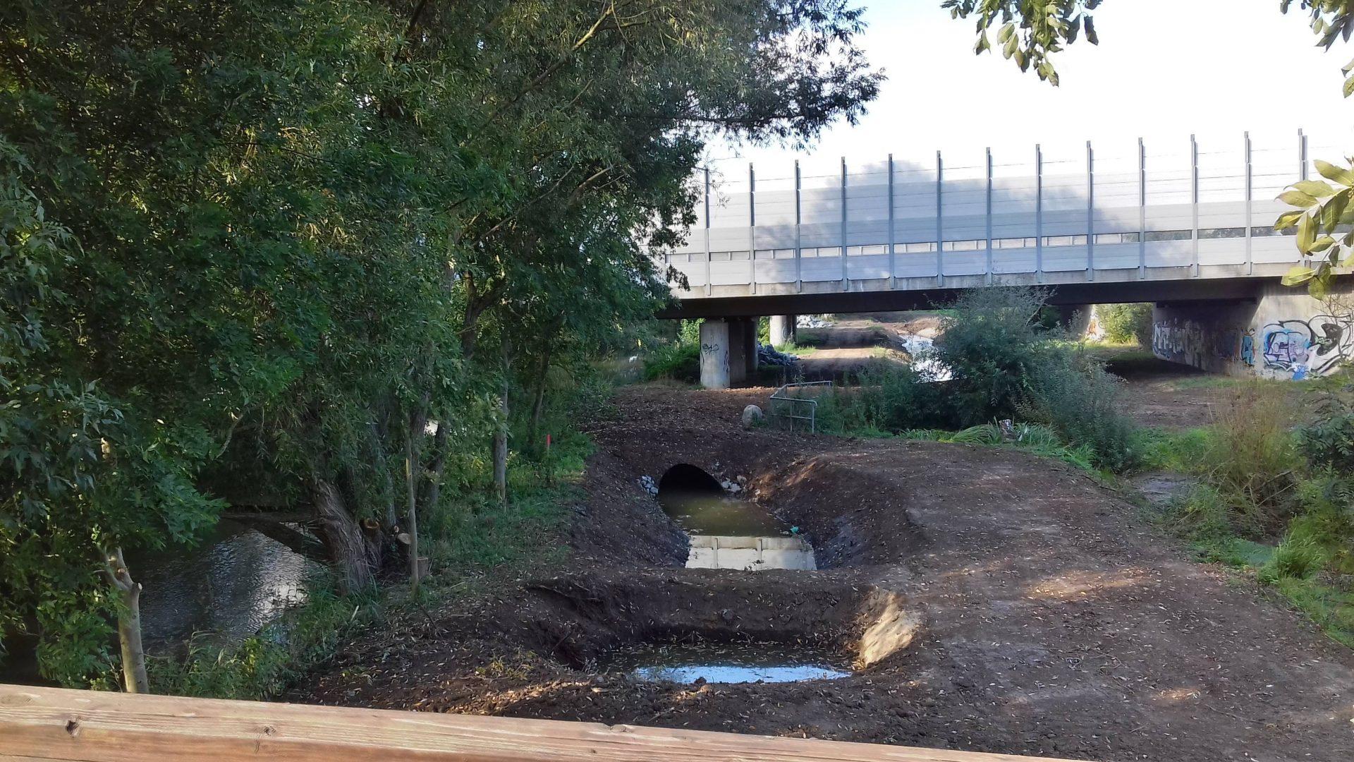 Man sieht eine Autobahnbrücke, darunter aufgeschüttete Baustraßen die wie Ameisenstraßen quer durchs Bild laufen